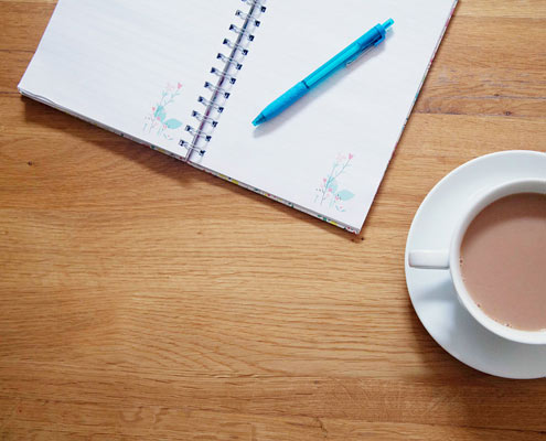 Copy and a writing book and pen and a cup of tea